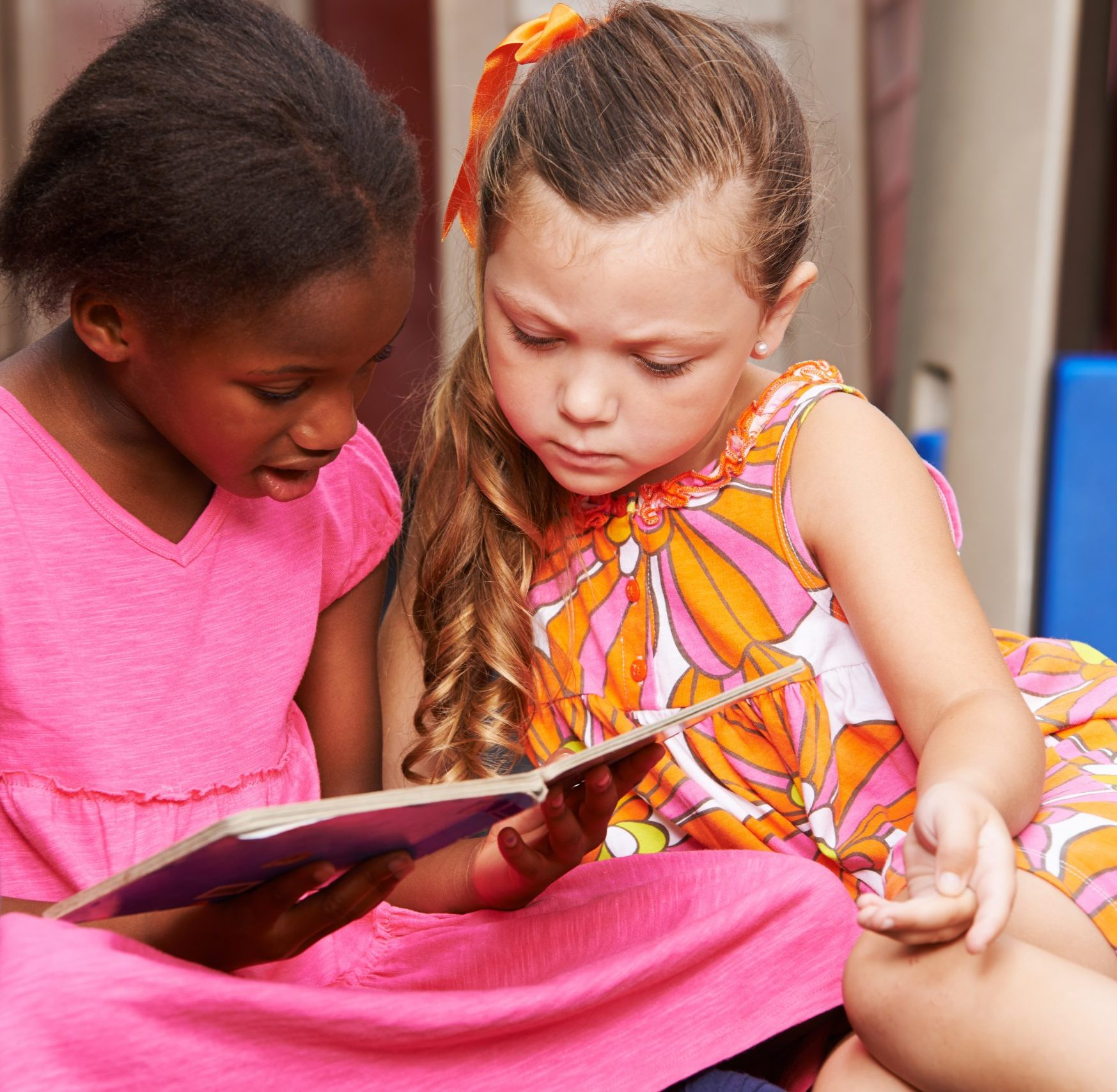 Two girls reading a book together