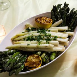 A dish of Asparagus with grilled lemon halves.