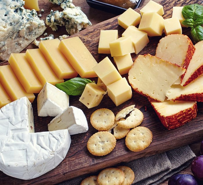 A cutting board full of different cheeses, crackers, and fruit