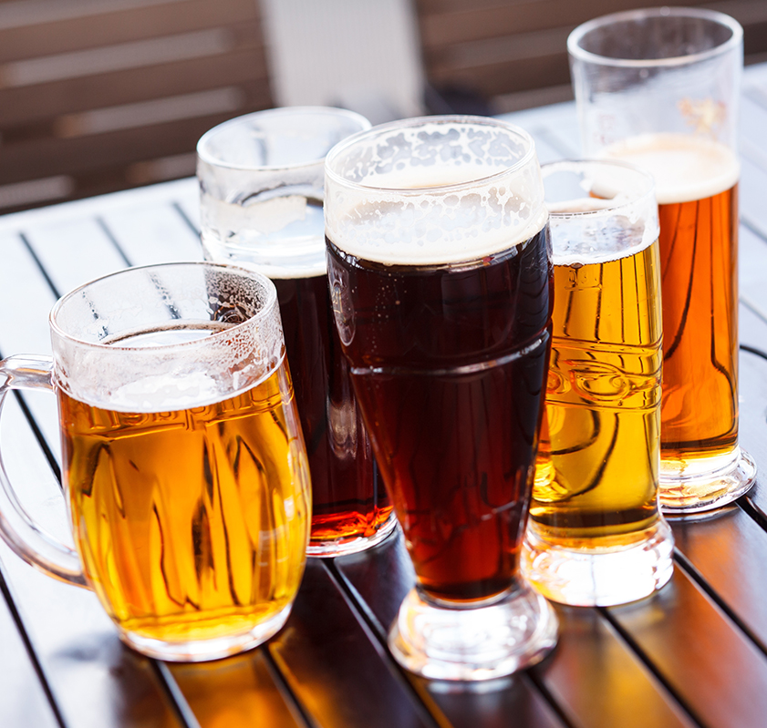Different mugs and glasses filled with different types of beer on a table