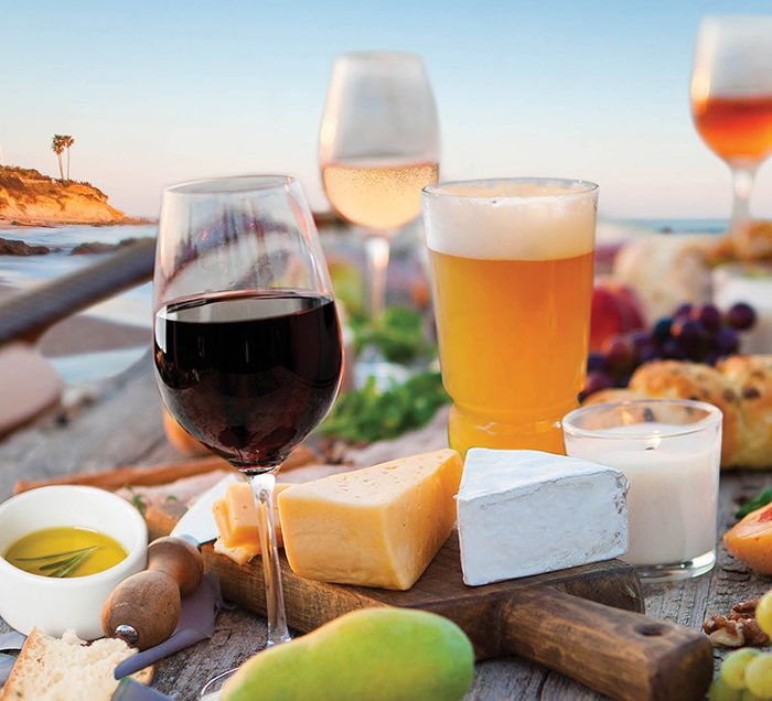 Cheese, wine, beer, and olive oil on a table at the beach