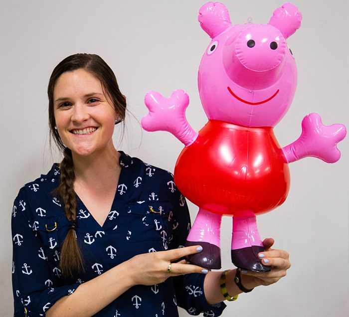 Girl holding blow up Peppa Pig