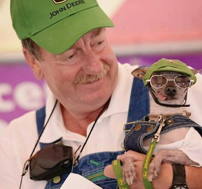 Man holding dog, both are wearing overalls and green hats