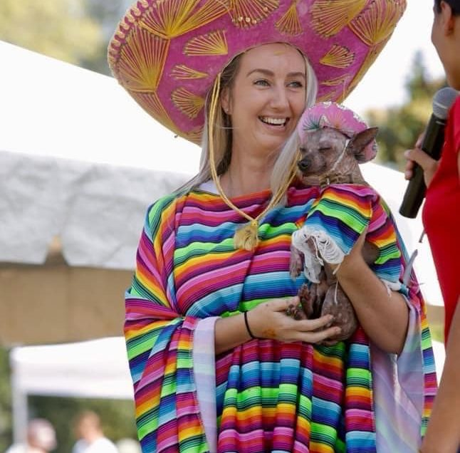 A lady and dog dressed the same with a sarape and sombrero