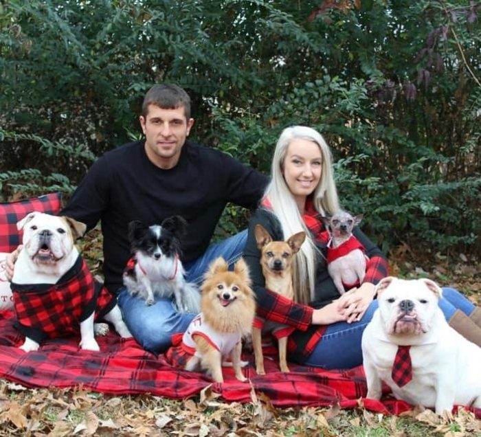 Two people sitting on a blanket with 6 dogs surrounding them