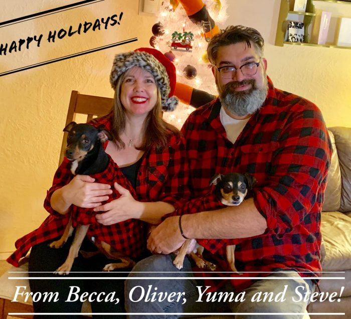 Two people sitting with two dogs all wearing matching plaid