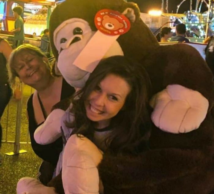 Two ladies holding a big monkey stuffed animal