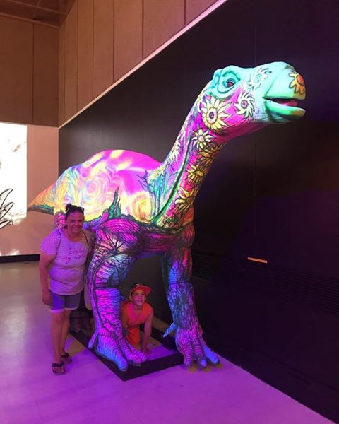An adult and child posing next to a dinosaur display with colorful light flashing on it