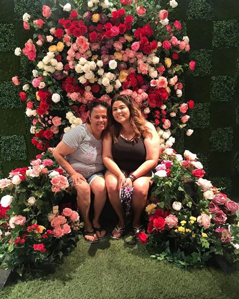 Two people sitting in a floral arranagement