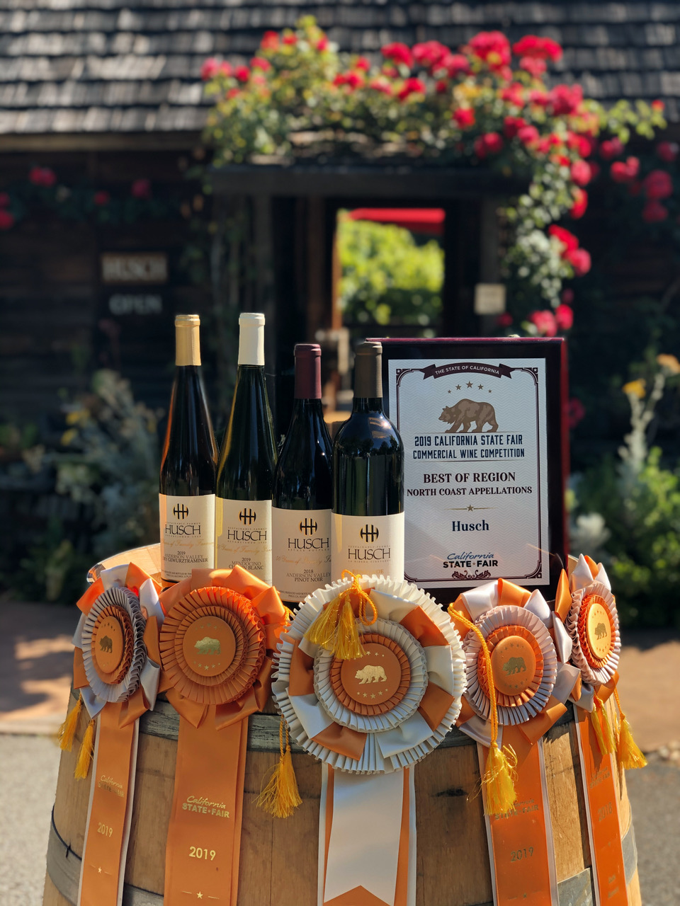 Wine bottles on a wood barrel with award ribbons hanging on the side