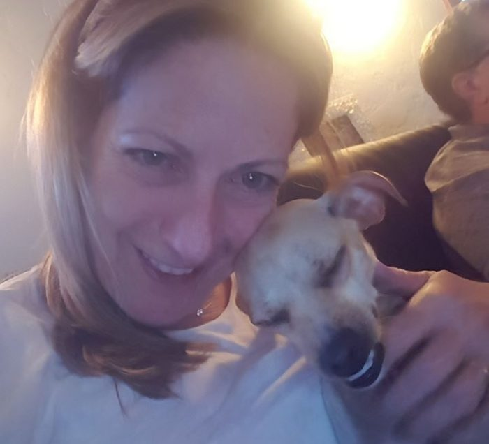 Person smiling with a dog leaning on her.