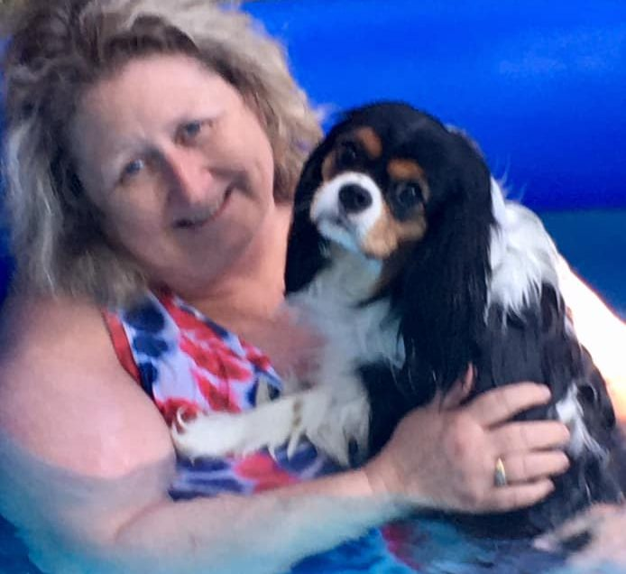 a smiling lady holding a dog in a swimming pool