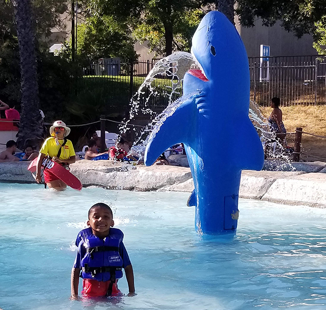A kid standing in a water pool with a toy shark spraying water