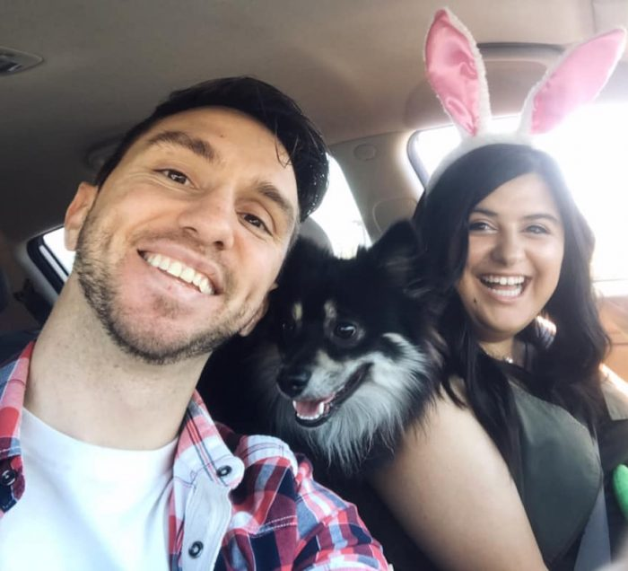 Two people sitting in a car with a dog between them