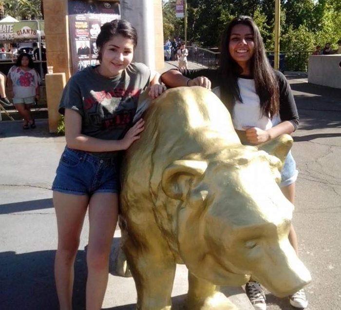 Two girls standing next to a golden bear