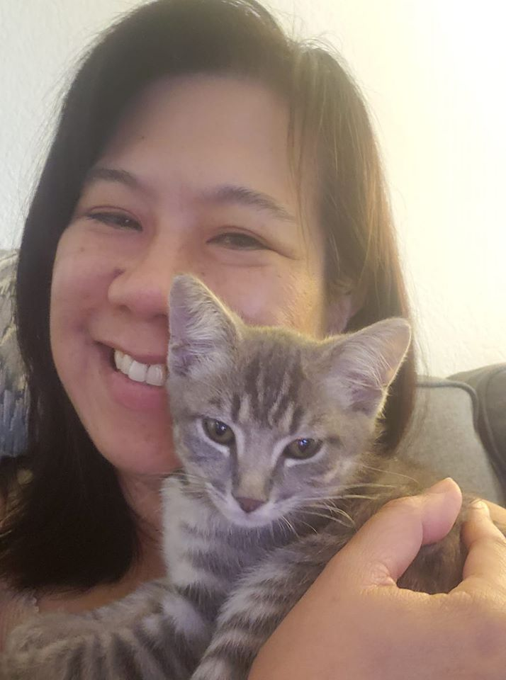A smiling lady holding their cat