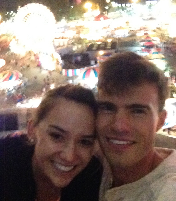 close up photo of two people on a ferris wheel with carnival lights in the background
