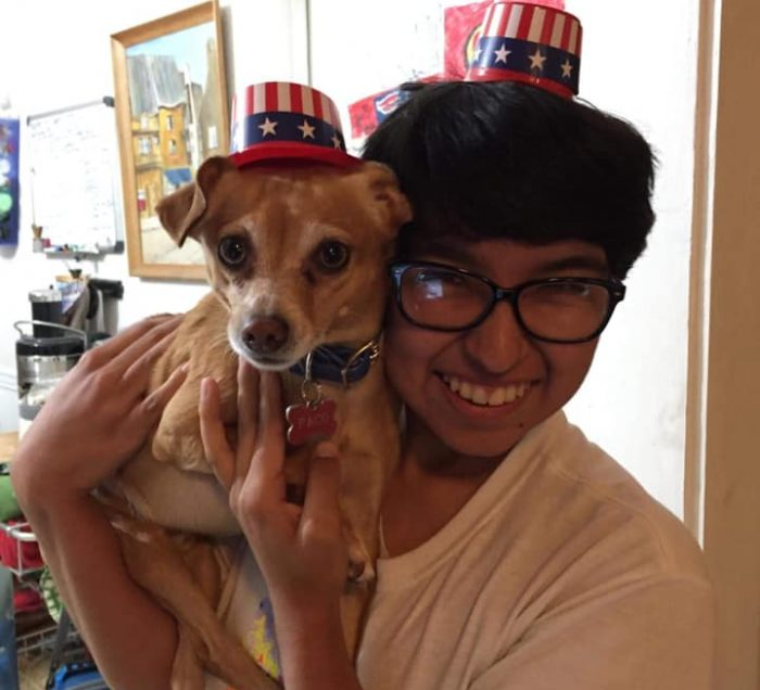 Person holding dog, both with matching hats on