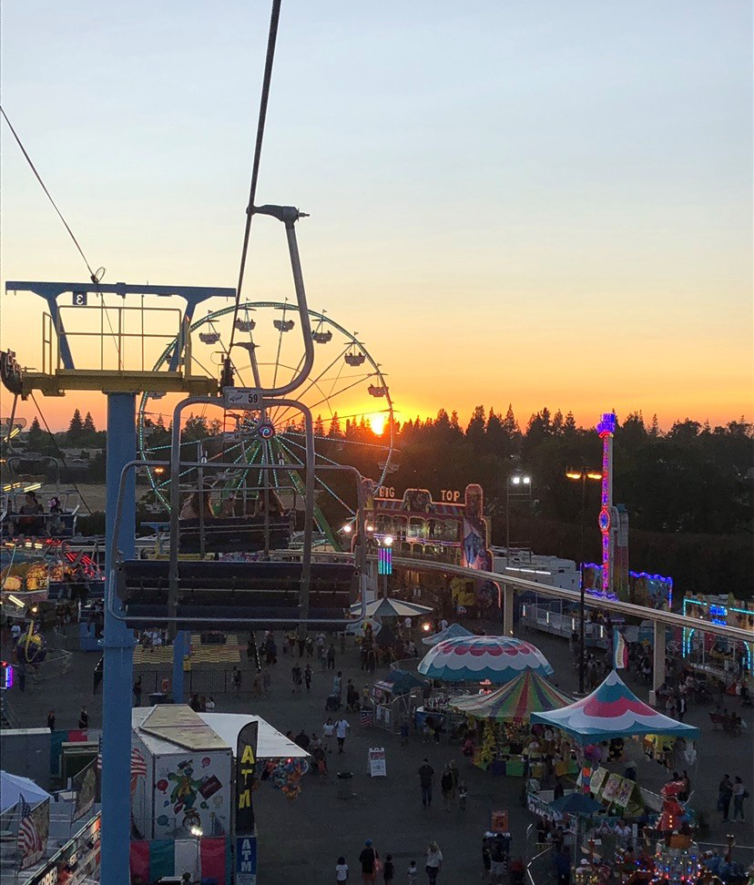 Sunset in the distance with Fair rides and tents below