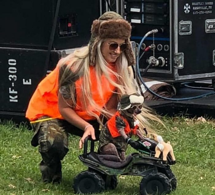 a lady pushing her dog that is sitting on a toy car