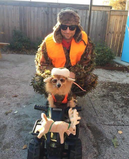 a man sitting behind their dog on a toy car