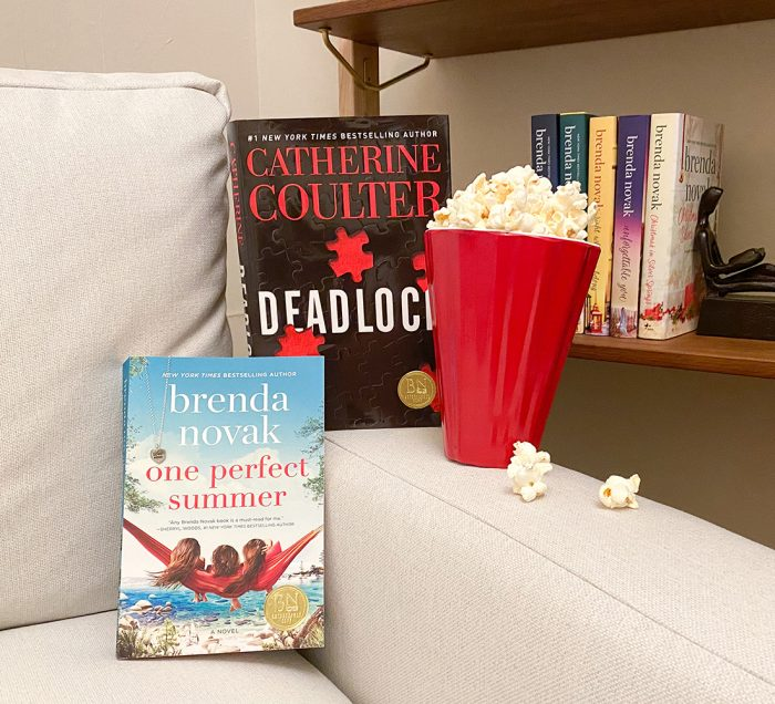Books resting in the corner of a couch with a container of popcorn. Bookshelf in background with books.