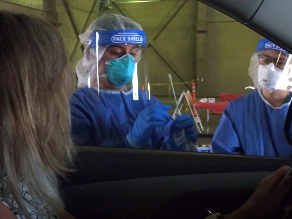 Woman in car with two nurses explaining the covid-19 testing