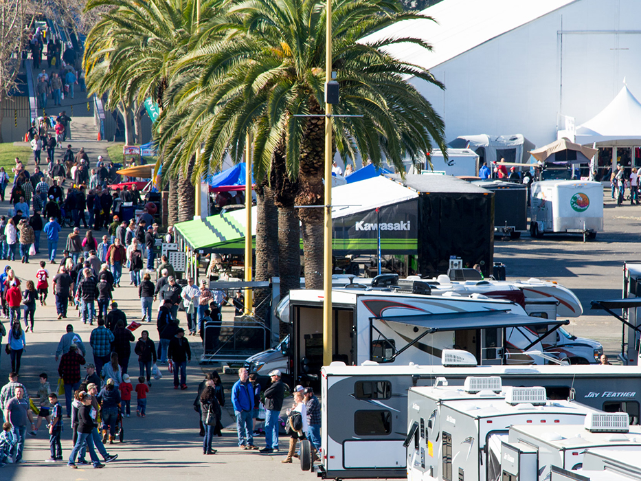 People walking at the International Sportsmen's Expo booths and line set up with people waiting around with RVs parked on the right