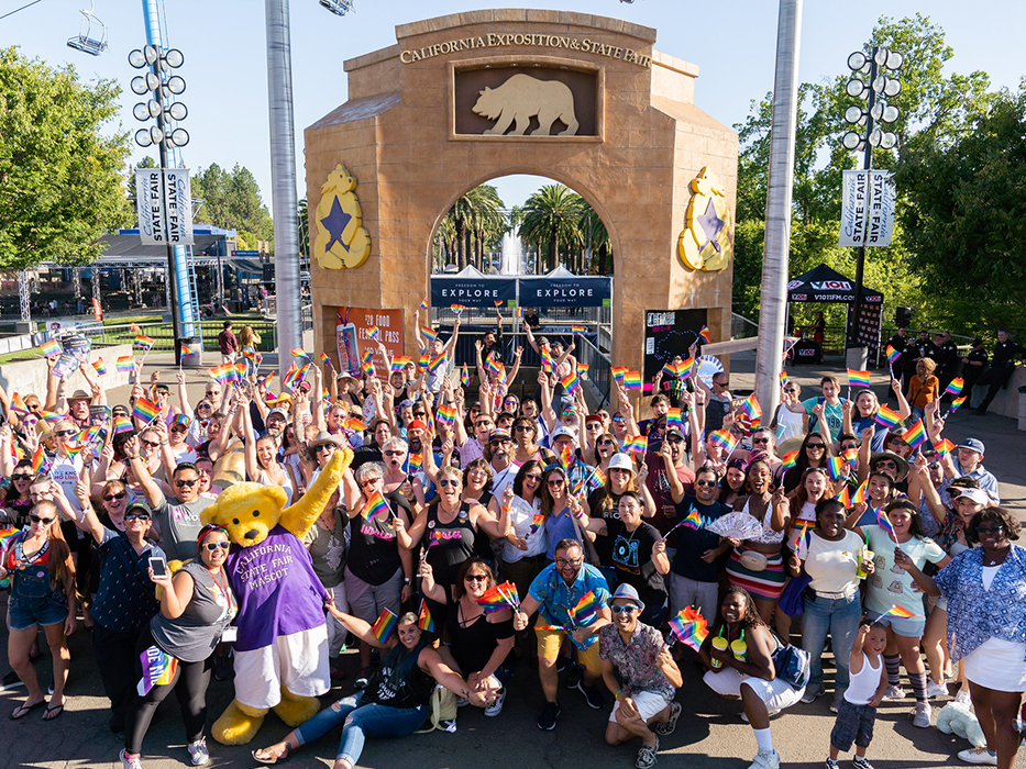 A large crowd of people posing together for a group photo with CA State Fair mascot, Poppy, at the Fair. For Out at the Fair group photo 2019