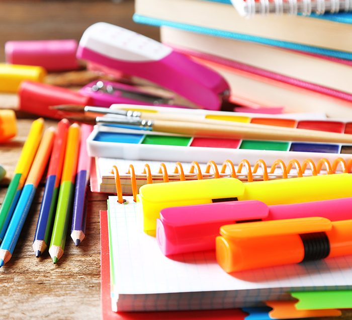 coloring pencils, stapler, pens, highlighters, notebooks, paper, erases scattered on a desk