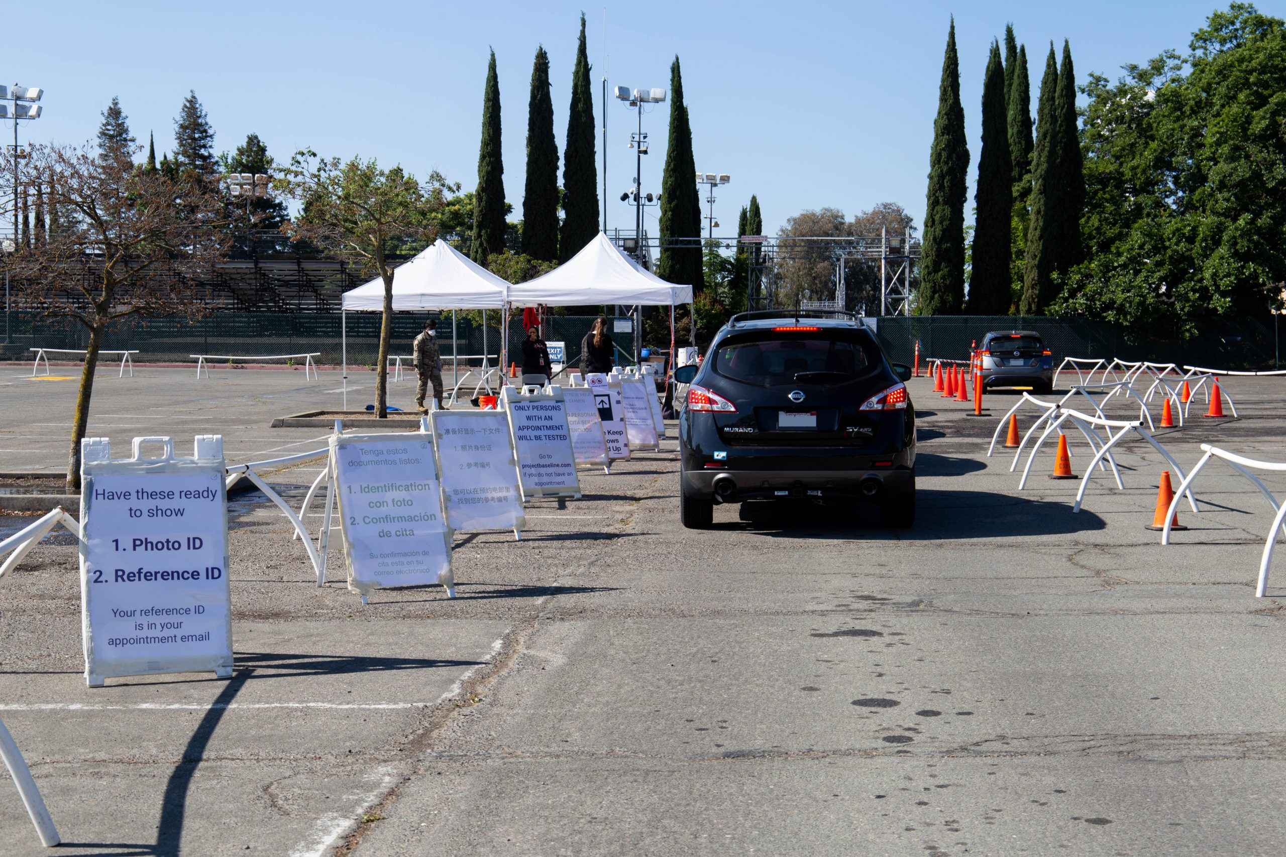 A car waiting in line for a covid-19 test. There are a-frame signs along the left with directions and pop up tents in the background.
