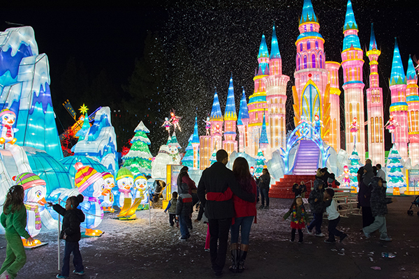 People looking at a light up, blow up castle at night