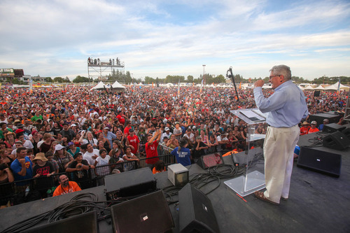 Large crowd of many people standing and watching a person give a speech on a stage
